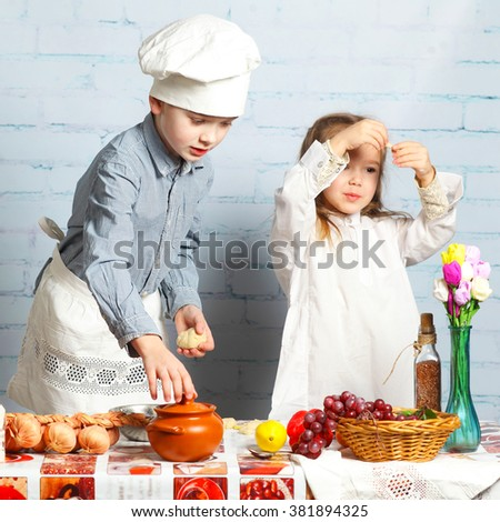 Children chefs. little brother and sister cook in the kitchen. Little boy preparing dough for bread.  - stock photo