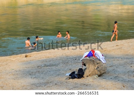 Children clothes while swimming at river near them school. - stock photo