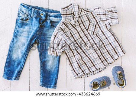 Children clothing  on wooden background - stock photo