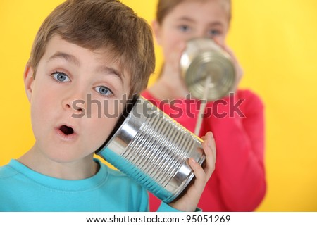 Children communicating with tin cans - stock photo