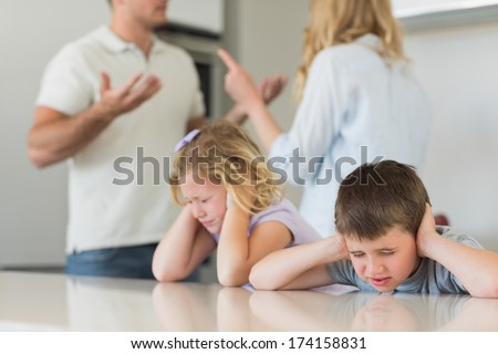 Children covering ears with hands while parents arguing in the background at home - stock photo
