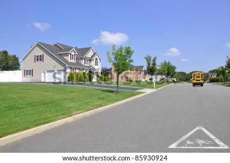 Children Crossing School Traffic Symbol on Residential Suburban Street School Bus Stop Sign Extended down the block Sunny Blue Sky Day - stock photo