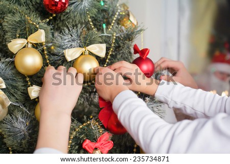 Children decorate the Christmas tree at Christmas and in the window watching them Santa Claus - stock photo
