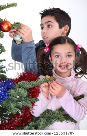 children decorating Christmas tree - stock photo