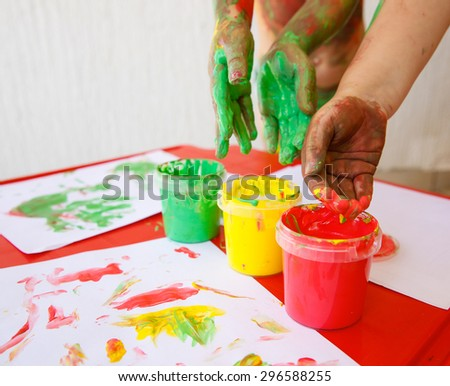 Children dipping fingers in washable, non-toxic finger paints, painting a drawing. Sensory play, innovative approach to learning, fun childhood concept.  - stock photo