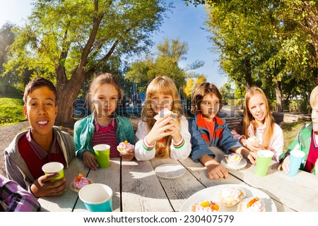 Children diversity drinking tea and eat outside - stock photo