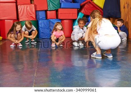 Children doing gymnastics in physical education with nursery teacher in preschool - stock photo