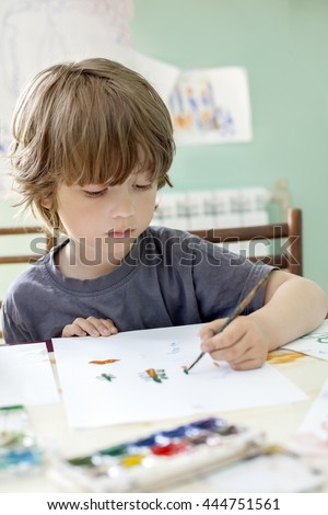 Children draw in home with watercolor and brush