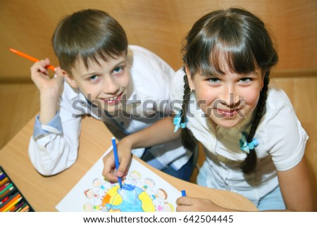 Children draw on paper. Creativity and education concept. The child paints with colored pencils on a white sheet of paper (table)