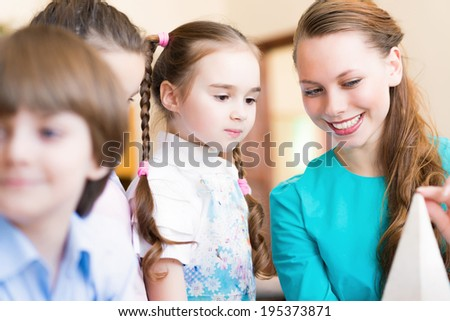 children draw with the teacher in the classroom drawing - stock photo