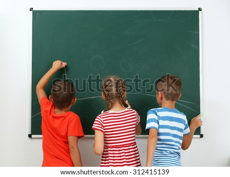 Children drawing on blackboard at school - stock photo