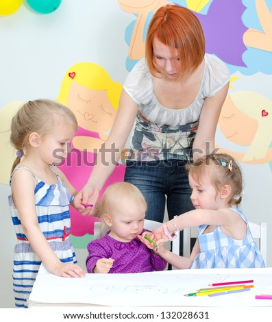 Children drawing with pencils in classroom - stock photo
