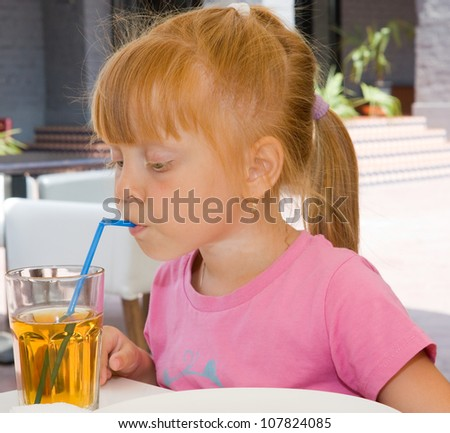 Children drinking fruit juice in cafe - stock photo