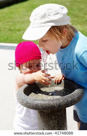 Children drinking water in a drinking fountain in park - stock photo