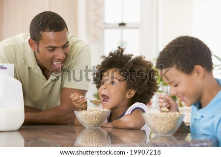 Children Eating Breakfast With Dad - stock photo