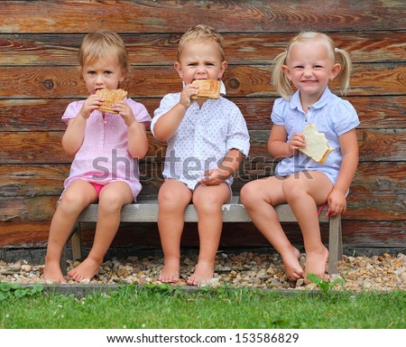 Children eating on the rural bench. - stock photo