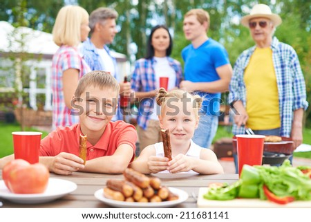Children eating sausages during their family gathering - stock photo