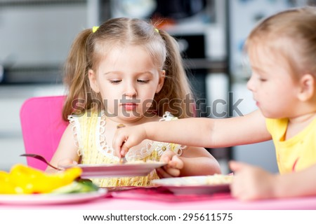 children eating spaghetti with vegetables in nursery or at home