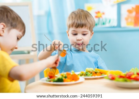 children eating vegetables in kindergarten or at home - stock photo