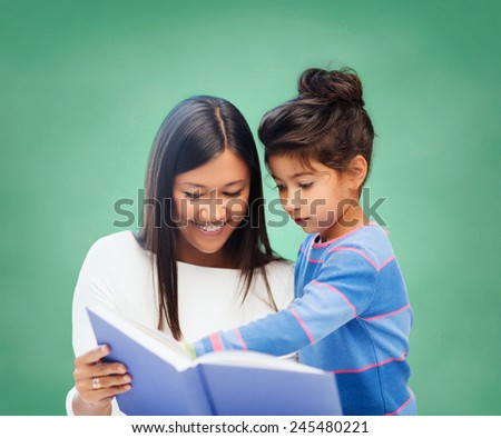 children, education, school and happy people concept - happy teacher and little schoolgirl reading book over green chalk board background - stock photo