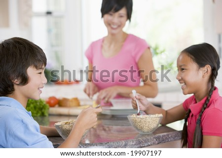 Children Enjoying Breakfast While Mother Is Preparing Food - stock photo