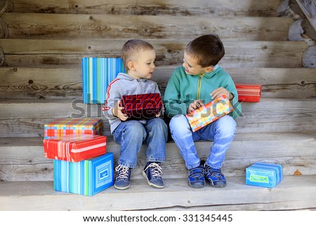 children exchanging gifts. two little brothers lovingly exchange gifts - stock photo