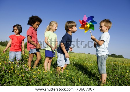 Children experiencing  alternative energy by blowing at windmill - stock photo