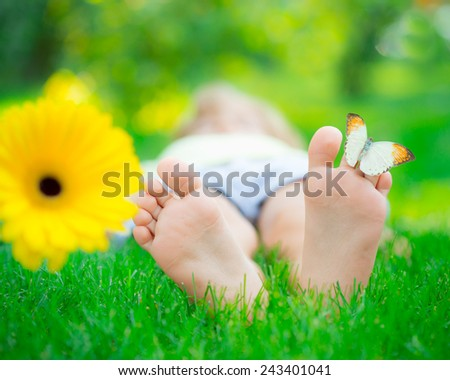 Children feet in green grass. Butterfly on spring flower - stock photo