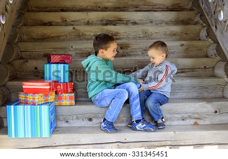 children fighting over a gift. two brothers playfully trying to seize gift - stock photo