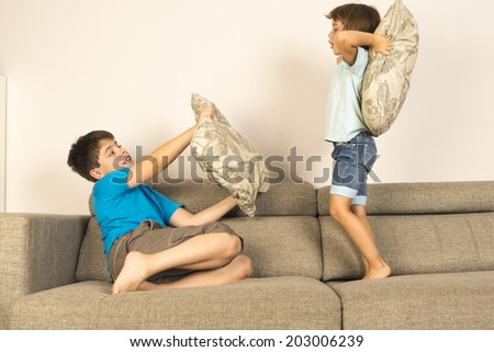 Children fighting together with pillows on sofa at home  - stock photo