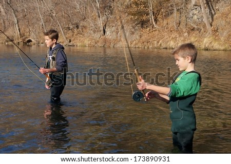 Children fishing - brothers and friends fly fishing in a clear stream (focus centered on boy casting in foreground) - stock photo