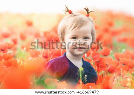 Children - flowers of life. Funny child holding a flower at outdoor at poppy field. Baby girl. Spring. ?hildren's Day celebrating on first June, 1 or 14 November