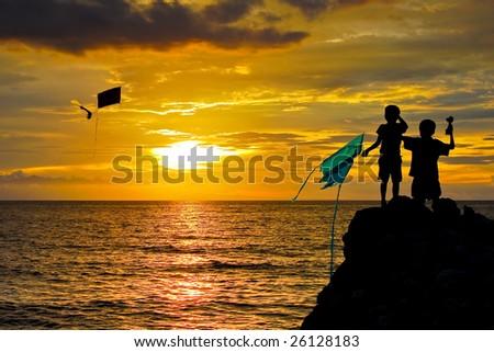 children flying kite at sunset - stock photo