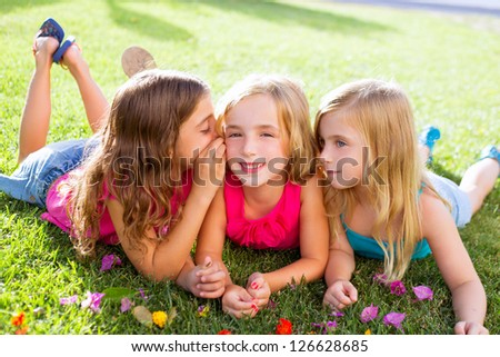 children friend girls group playing whispering on flowers grass in vacations - stock photo