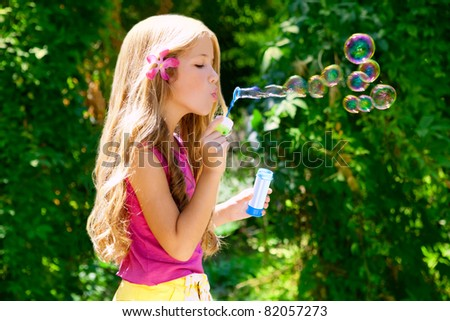 Children girl blowing soap bubbles in outdoor forest - stock photo
