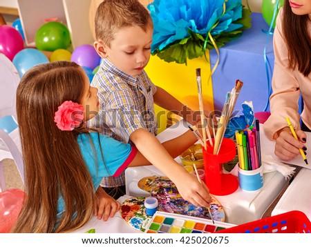 Children girl boy and  teacher woman  at table  in  kindergarten school.  - stock photo