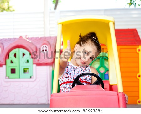 children girl driving a toy car with ok hand gesture in playground - stock photo