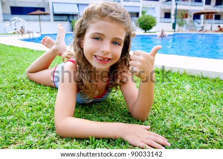 children girl lying on grass in pool during summer vacation - stock photo
