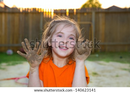 children girl playing with mud sand ball and dirty hands smiling happy