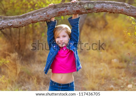 children girl swinging in a tree trunk in a pine forest - stock photo