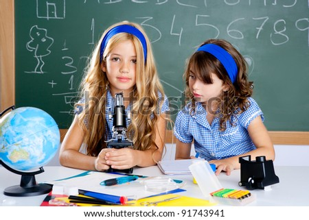 children girls at school classroom with world map and microscope
