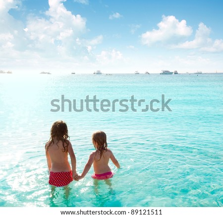 children girls rear view in the beach looking at sunset - stock photo