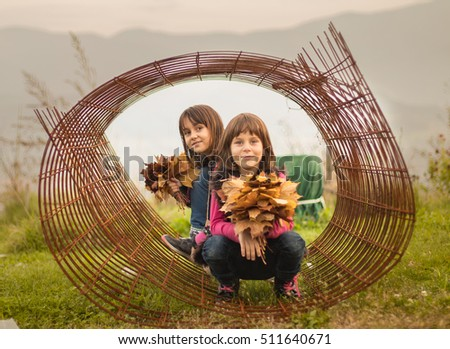 Children girls sisters play in Rolls of steel wire mesh outside on mountain background. Alternative toys, safety.