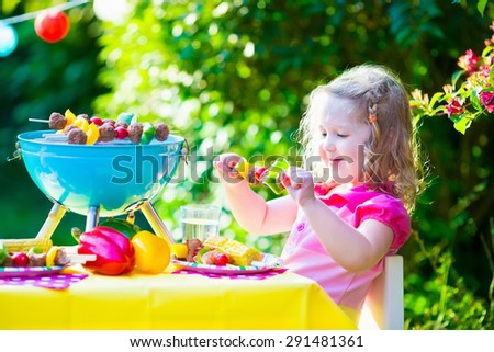 Children grilling meat. Family camping and enjoying BBQ. Little girl at barbecue preparing steaks, kebab and corn. Kids eating grill and healthy vegetable meal outdoors. Garden party for toddler child - stock photo