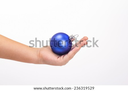 Children hand holding blue Christmas ball isolated on white background