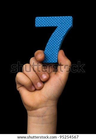 Children hand holding the number Seven. Black isolated blue color number Seven - stock photo