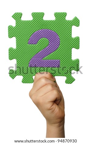 Children hand holding the number Two. White isolated multicolor number Two - stock photo