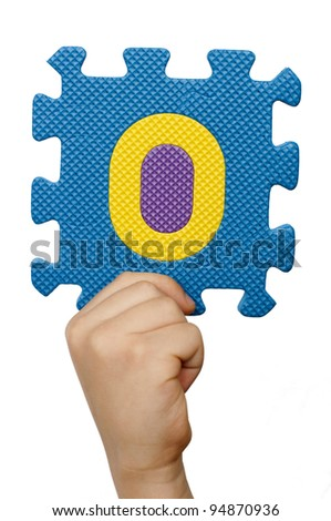 Children hand holding the number Zero. White isolated multicolor number Zero - stock photo