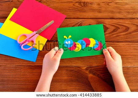 Children hands holding paper applique caterpillar. Paper sheets, scissors on a brown wooden background  - stock photo