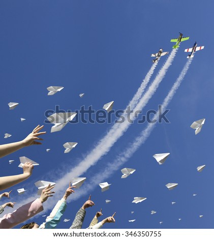 Children hands throw upward a lot of messages in the manner of paper airplanes. In the same time three sport aircraft are climbing in the blue sky straight above them.
